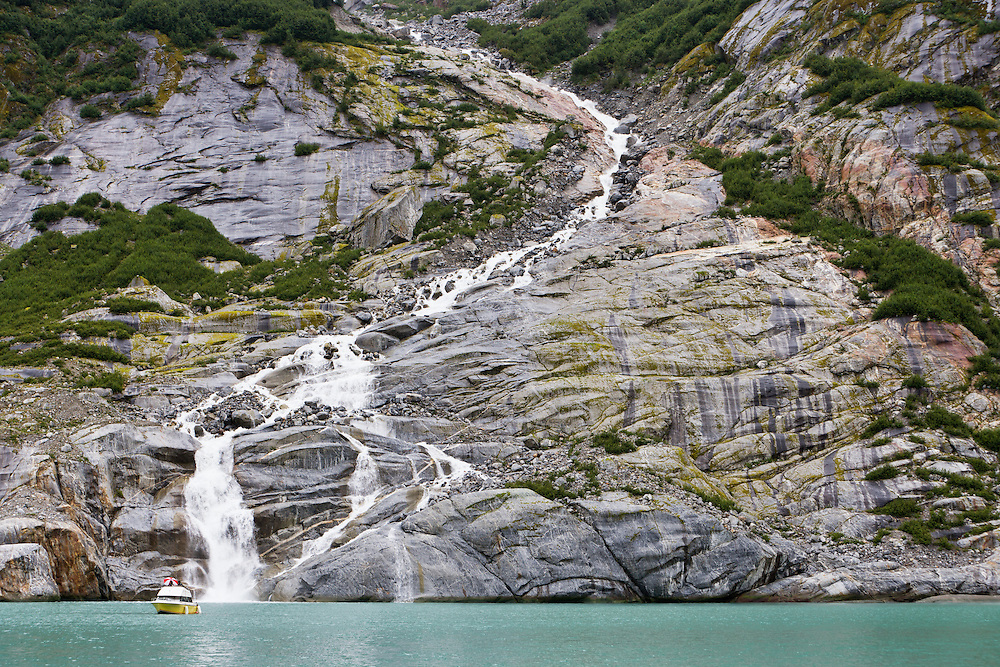 Tourist boat near base of unnamed waterfall in Endicott Arm fjord near Dawes Glacier in Tracy Arm - Fords Terror Wilderness in the Inside Passage of Southeast Alaska. Summer. Afternoon.