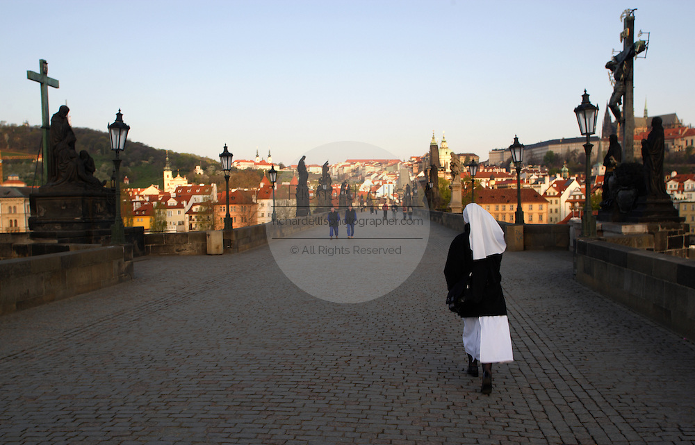 A nun walks across the historic Charles Bridge built in the 14th century with rows of Baroque statues during early morning in Prague, Czech Republic.
