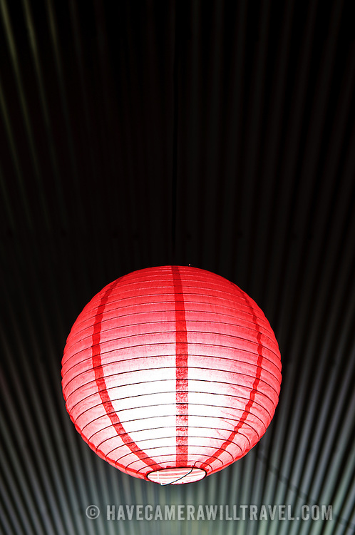 Red light fixture against the lines of a corrugated iron roof