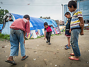 05 AUGUST 2015 - KATHMANDU, NEPAL: Boys play marbles in a large Internal Displaced Person (IDP) Camp in the center of Kathmandu. The camp is next to one the most expensive international hotels in Kathmandu. More than 7,100 people displaced by the Nepal earthquake in April live in 1,800 tents spread across the space of three football fields. There is no electricity in the camp. International NGOs provide water and dug latrines on the edge of the camp but the domestic waste water, from people doing laundry or dishes, runs between the tents. Most of the ground in the camp is muddy from the running water and frequent rain. Most of the camp's residents come from the mountains in northern Nepal, 8 - 12 hours from Kathmandu. The residents don't get rations or food assistance so every day many of them walk the streets of Kathmandu looking for day work.      PHOTO BY JACK KURTZ