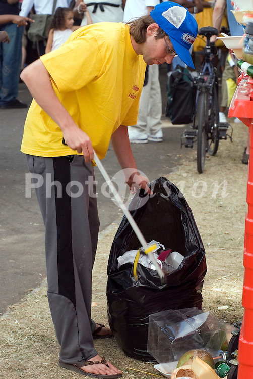 Man cleaning and clearing rubbish at Lambeth Country Show; Brockwell Park; South London July 2006 UK