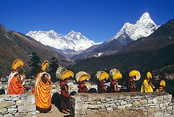 Buddhist Mani-Rimdu festival at Tengboche Monastery, Buddhist monks of yellow-hat sect play drums in procession, Ama Dablam (on right) and Mt. Everest (center) in background