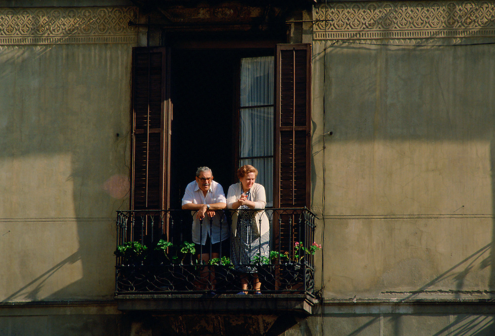 Elderly man and woman watching from the balcony of their home in Seville,Spain