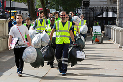 © Licensed to London News Pictures. 08/08/2019. London, UK. Peoples Vote activists dressed as waste collectors prepare dump filled bin bags and plastic rats outside the Cabinet Office. They are protesting against a No Deal Brexit .  Photo credit: George Cracknell Wright/LNP