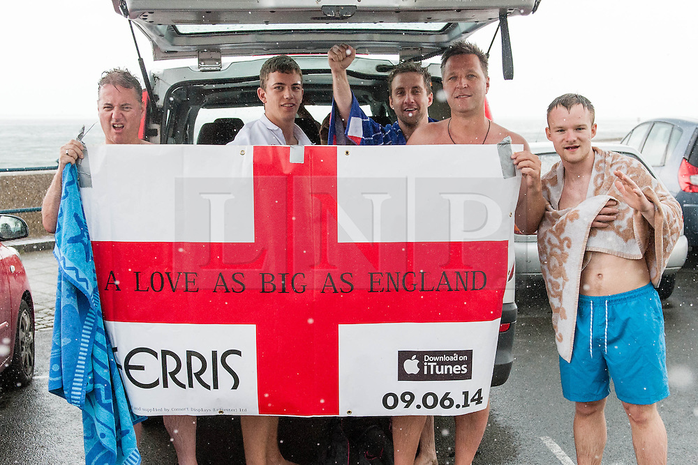 © Licensed to London News Pictures. 14/06/2014. Ryde, Isle of Wight, UK. English football fans show a St Georges Cross banner as they shelter beneath the boot door of their car during a sudden thundery downpour.  Tonight England will be playing their first match of the World Cup against Itally.   Moments earlier the weather was hot & sunny - the UK is experiencing a period of hot sunny weather with temperatures over the weekend expected to reach 74 F (23 C).  Photo credit : Richard Isaac/LNP