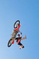 Freestyle motocross racer performing stunt in air