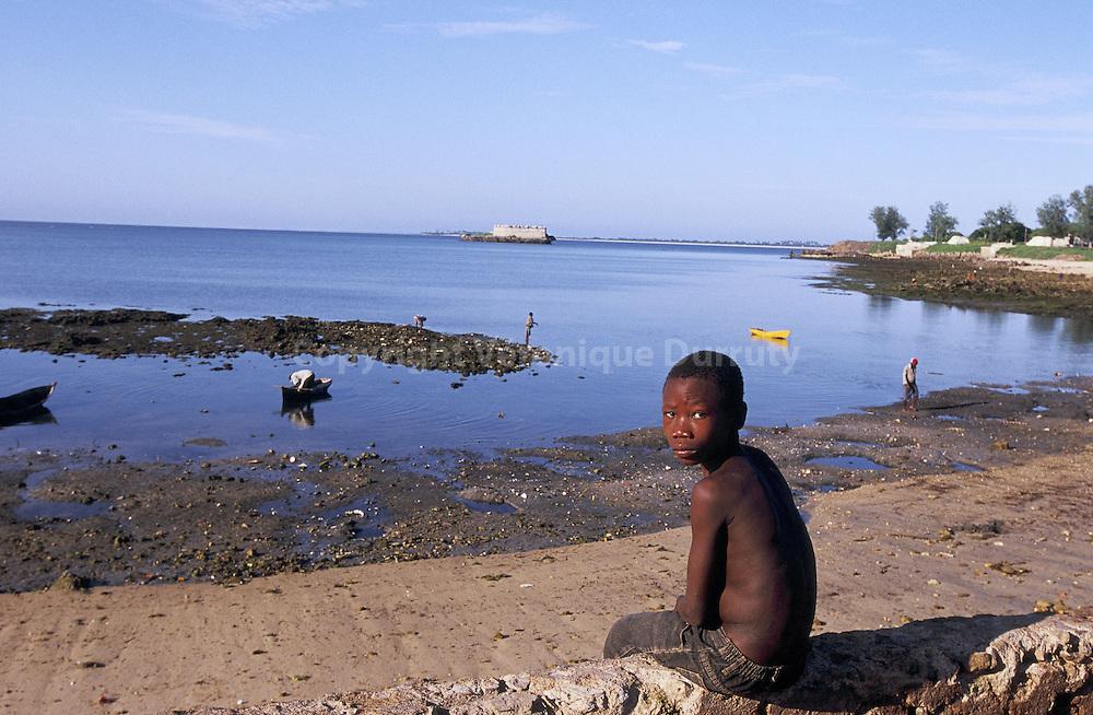 Child facing the sea. Since the slaves market stop, and the capital change in Maputo, the island is suffering of poverty. // Enfant face a la mer. Depuis l'arret du traffic d esclaves, puis le transfert de la capitale a Maputo, l ile souffre de pauvrete.