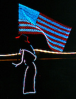 A woman on horseback wearing an illuminated suit and hat rides into the rodeo arena with the American flag at the National Western Stock Show in Denver, Colorado January 16, 2007. REUTERS/Rick Wilking (UNITED STATES)