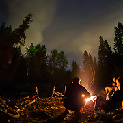 Heidi, Reiley, Rex and Anlyn Flake along with Yuri Choufour sit by a fire along a river near Leavenworth, Washington.