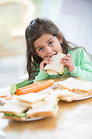 Portrait of girl eating sandwich at home