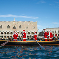 VENICE, ITALY - DECEMBER 26: Rowers dressed as Father Christmas escort a gondola ferring a live nativity scene from St Mark's to the Island of S Giorgio on December 26, 2011 in Venice, Italy.  The event is in its first year wants and to replicate an ancient tradition when the Doge of Venice used to go to the Island of S Giorgio to celebrate the relics of Santo Stefano on Boxing Day. HOW TO LICENCE THIS PICTURE: please contact us via e-mail at sales@xianpix.com or call our office London   +44 (0)207 1939846 for prices and terms of copyright. First Use Only ,Editorial Use Only, All repros payable, No Archiving.© MARCO SECCHI