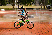 05 AUGUST 2020 - DES MOINES, IOWA: A child rides a bike through a splash pad in Evelyn K. Davis Park in Des Moines.     PHOTO BY JACK KURTZ