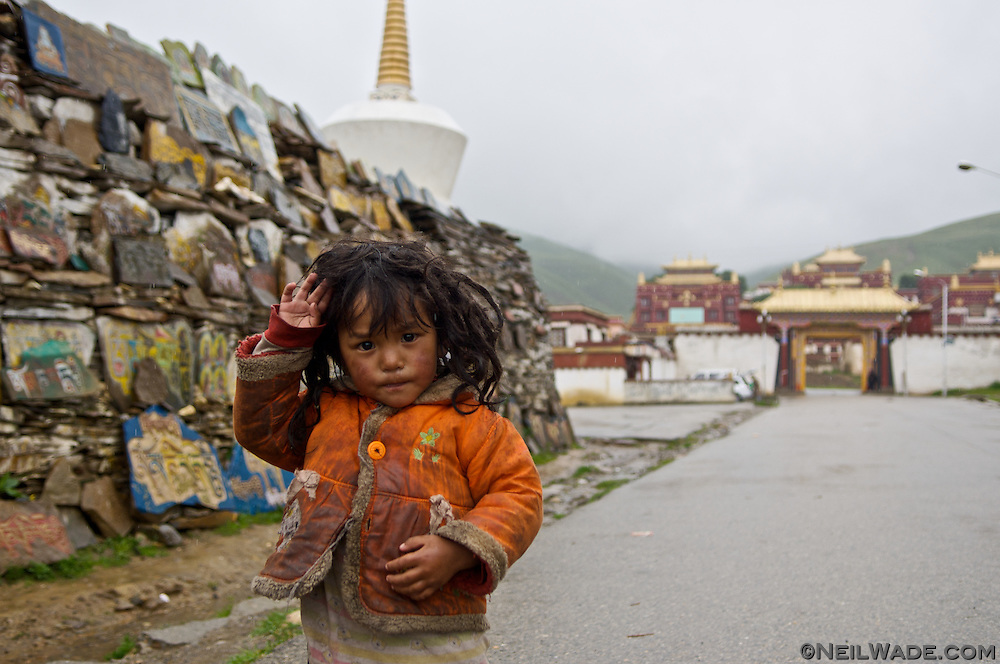 A girl stands in the rain next to a big mani stone pile in front of the Litang Cho?de Monastery in Litang, Tibet.  Mani stones are prayers carved into rocks then piled up near important religious places.