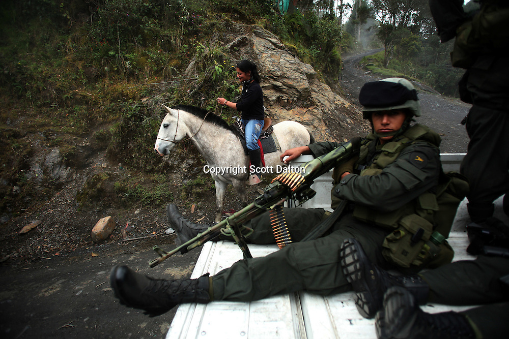 A young woman rides her horse by a patrol of Jungla, a unit of the Colombian anti-narcotics police, while they are searching for a cocaine lab in a remote part of Cundinamarca state in central Colombia, on June 29, 2007. (Photo/Scott Dalton)