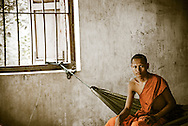 A monk sitting by the window in Siem Riep, Cambodia