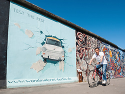 Man cycles past painting of Trabant car on wall at East Side Gallery at former Berlin Wall in Friedrichshain/Kreuzberg in Berlin Germany