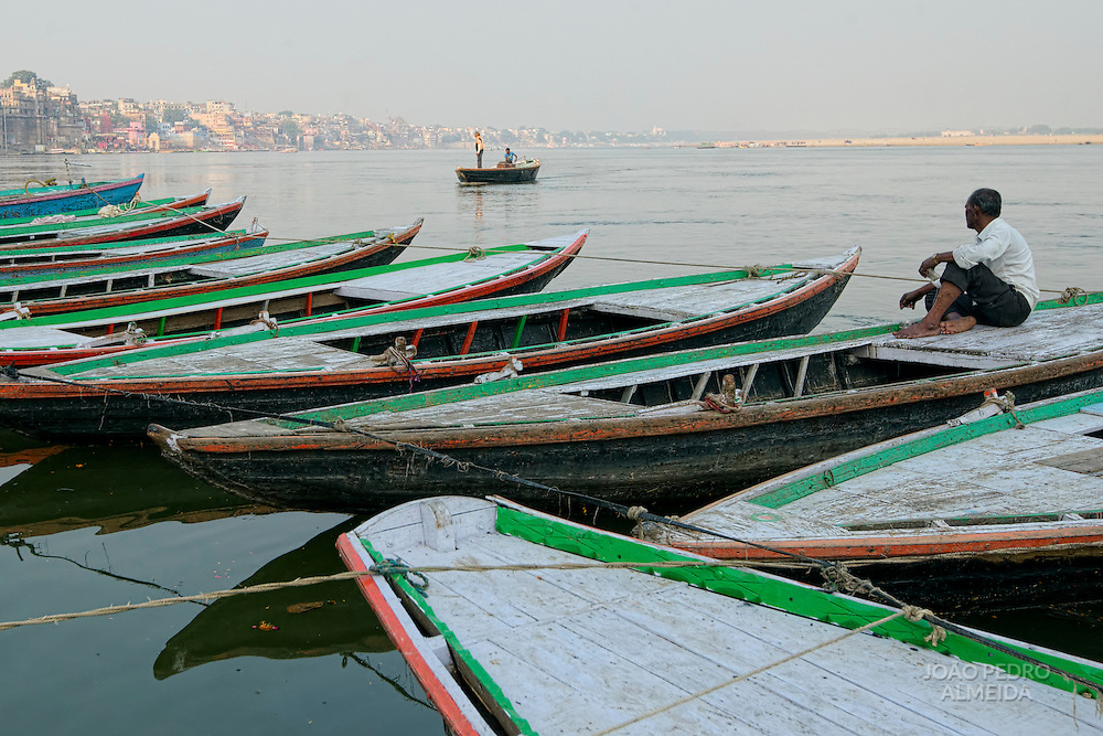 Boatman sitting at anchored rowboats at the end of the day.