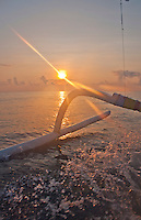 Rising sun over the ocean, sen through the outrigger and the splashing wake on the way to Nusa Penida.