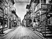 Rue du Petit Champlain in old Quebec City with its colorful shop windows and restaurants. Pot en Ciel, le Souvenoit and other stores, Quebec, Canada. Black and white photo. Ville de Québec.