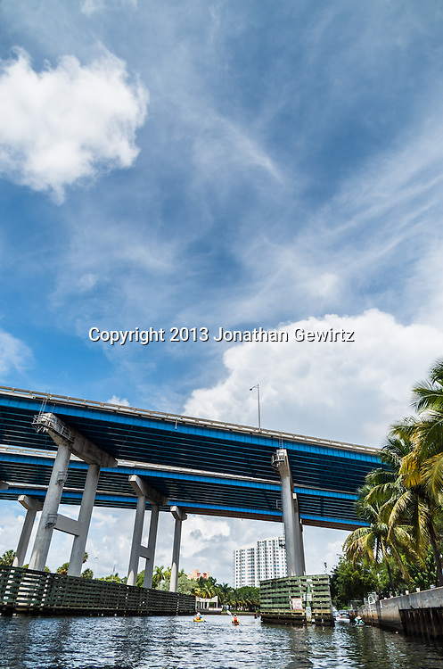 Kayaker paddle under US Route 95 as it passes over the Miami River to the West of downtown Miami, Florida. WATERMARKS WILL NOT APPEAR ON PRINTS OR LICENSED IMAGES.