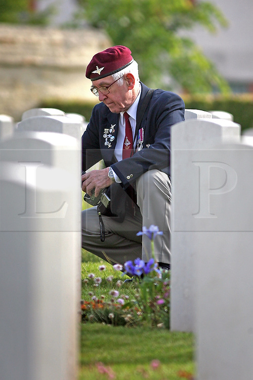 06/06/2009 A veteran member of the Parachute Regiment pays his respects at a gravestone during the 65th D-Day Anniversary Service, Ranville, France.