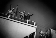 Jubilent Central American migrant men ride atop northbound freight train they just mounted in Lecheria train depot, Mexico City, Mexico.