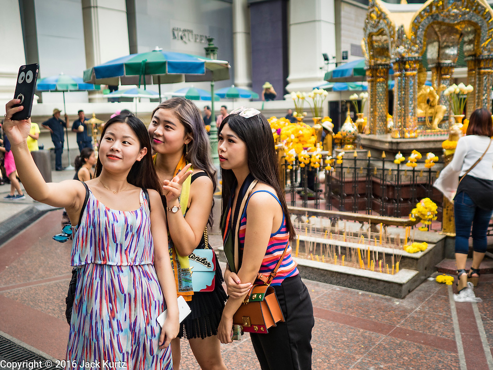 16 AUGUST 2016 - BANGKOK, THAILAND: Tourists pose for selfies at Erawan Shrine one year after the shrine was bombed in the worst international terrorist attack in Thai history. On 17 August 2015, a bomb was set off at the Erawan Shrine, a popular tourist attraction and important religious shrine in the heart of the Bangkok shopping district. According to the Royal Thai Police  20 people were killed in the bombing and 125 injured. Most of the people killed in the bombing were tourists from other Asian countries. Thai Police arrested an alleged Uighur extremist for the bombing. The case against him is still pending in Thai courts. The shrine was repaired, rededicated and reopened to the public on 4 September 2015.      PHOTO BY JACK KURTZ