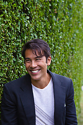 PhotoLibrary-RJ Asian American man smiling and standing by a hedge in East Hampton, NY