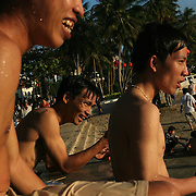 """Young men grab a snack after swimming off the beach in Vung Tau, Vietnam, a popular beach resort a few hours' drive from Ho Chi Minh City. Former glam rock star Gary Glitter is currently behind bars in the resort town, facing charges of child molestation. Glitter, whose real name is Paul Gadd, was convicted in Britain in 1999 of possessing child pornography and served two months in jail. In 2002 he was kicked out of Cambodia, a country with lax regulation of prostitution. Glitter's 1970's hit """"Rock and Roll (Part 2)""""  is played regularly at sporting events throughout North America and Europe."""