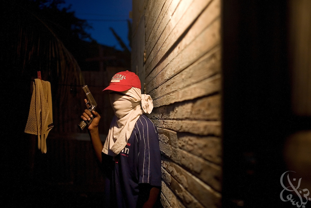 """A Jamaican ghetto """"Shotta"""" (shooter, or gunman) is seen with his face obscured to protect his identity in the Mountain View district of the Jamaican capital, Kingston December 08, 2008. Jamaica is struggling to contain the violence of such ghetto shottas as it faces a grim count for the year 2008 of more than 1600 murders, placing it among the most deadly places in the world per capita. ."""