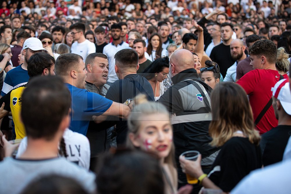 © Licensed to London News Pictures . 11/07/2018. Manchester, UK. Security guards intervene in a fight . Football fans watch England play against Croatia in the World Cup semi finals, on a big screen at Castlefield Bowl in Manchester City Centre . Until today , Manchester had been the largest city in England not to be showing World Cup matches to the public on a big screen . Photo credit: Joel Goodman/LNP