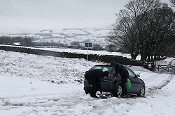 © Licensed to London News Pictures.04/03/16. Ilkley, UK.  Two teenagers in Ilkley try to free their car after it became stranded following heavy snowfall over night in Yorkshire caused chaos on many roads. Forecasters are predicting more cold weather this week as Storm Jake takes hold. Photo credit : Ian Hinchliffe/LNP
