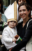 A mother holds her child, who is dressed in a bishop's hat for a Halloween Parade in Queens, New York.