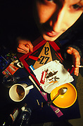 Man with grass on cluttered table spliff in hand 2000