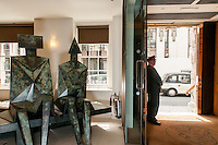 """Lynn Chadwick's sculpture """"Sitting couple on bench"""" in Christie's King street lobby with Colin Kemp the doorman."""