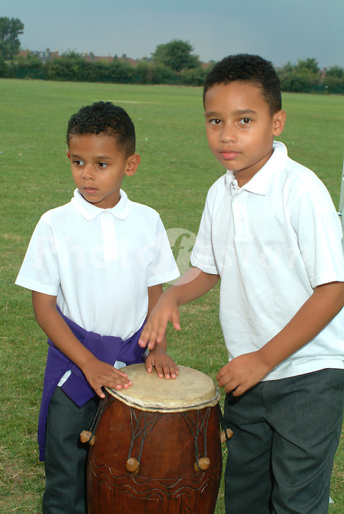 Boys playing on drums at fun day East London UK