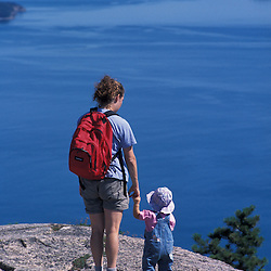 Acadia National Park, ME..A mother and her young daughter on the summit of Champlain Mountain.  Frenchman Bay is in the distance.