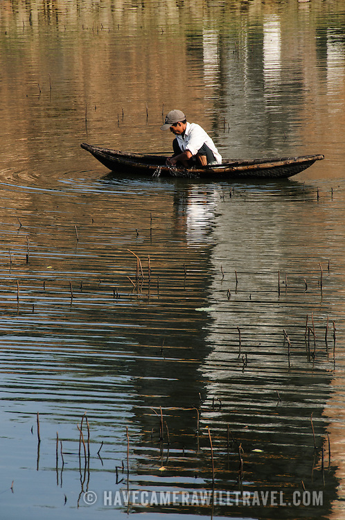 A fisherman casts his net in the shallow waters next to reeds in Hue, Vietnam.