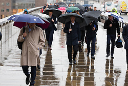 © Licensed to London News Pictures. 08/05/2019. London, UK.  Commuters cross London Bridge during rain and wet weather this morning.  Photo credit: Vickie Flores/LNP