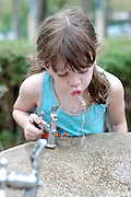 Young girl of 4 drinks water from a water fountain