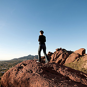 A hiker takes in the view from Camelback Mountain, Phoenix, Arizona.