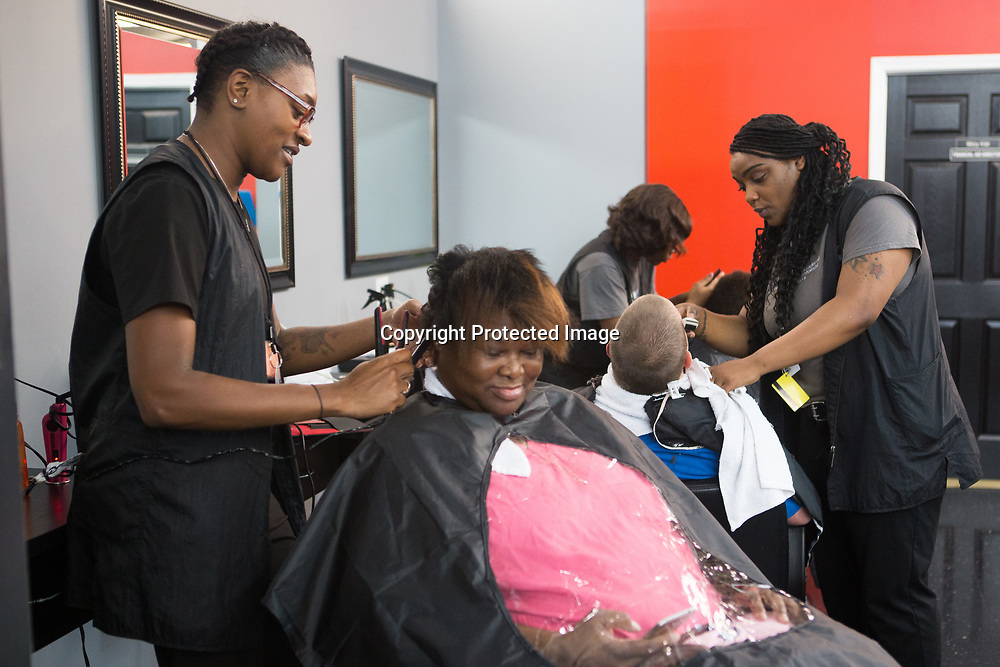 Students Asia Rosebud, left, and Anecia Harris, right, work on clients Tesha Watkins and Michael Fuller's hair Thursday night during the free haircut night at the Tupelo Academy of Cosmetology. In addition to hair, students learn how to do nails and facials.