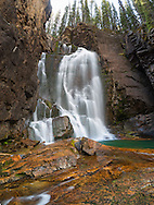 Beartooth Falls is an impressive sight at any time of year with its red rocks and green pools.
