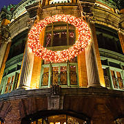 The Hotel du Capitole in Quebec City's Old Town at night, with a Christmas wreath decorating the main front of the building.