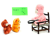 Teddy Bear in a class room environment teaches two smaller teddy bear dolls  on white background