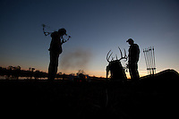 Hunters silhouetted in camp at sunset
