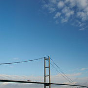 The Humber Suspension Bridgewith a plane passing high above at the Humber Estuary in Yorshire, England.