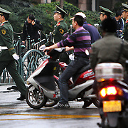 Shanghai, China. Soldiers stop traffic as they cross a street near Shanghai Museum of ancient Chinese art, situated on the People's Square in the Huangpu District of Shanghai. Shanghai is one of the most densely populated cities in China with over 24 million residents. Jose More Photography               .