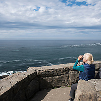 A senior couple whale watching with binoculars in the Pacific Ocean on the Oregon Coast at Cape Arago State Park near Coos Bay, Oregon.