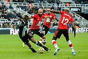 Allan Saint-Maximin (#10) of Newcastle United attempts to turn away from the challenge of Nathan Redmond (#22) of Southampton during the Premier League match between Newcastle United and Southampton at St. James's Park, Newcastle, England on 8 December 2019.